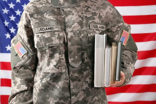 Close up view of female soldier holding books, with USA flag on background
