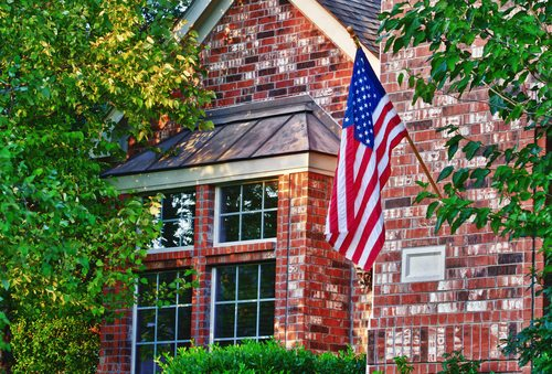 American flag hanging in front of brick house