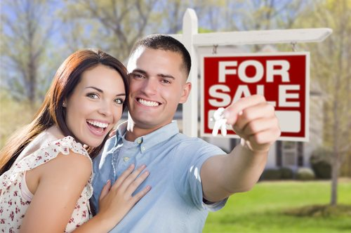 "Military Couple In Front of New Home with New House Keys and ""For Sale"" Sign Outside."