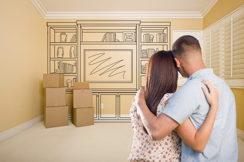 Hugging Military Couple In Empty Room with Shelf Design Drawing on Wall.