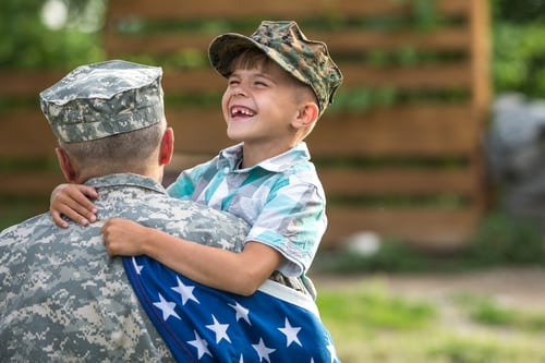smiling boy holding an American flag and hugging his father, who is wearing military uniform