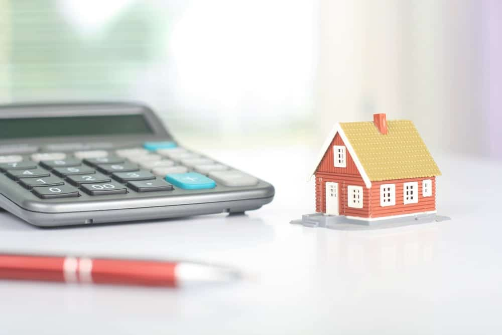 calculator, pen, and mini house on a table