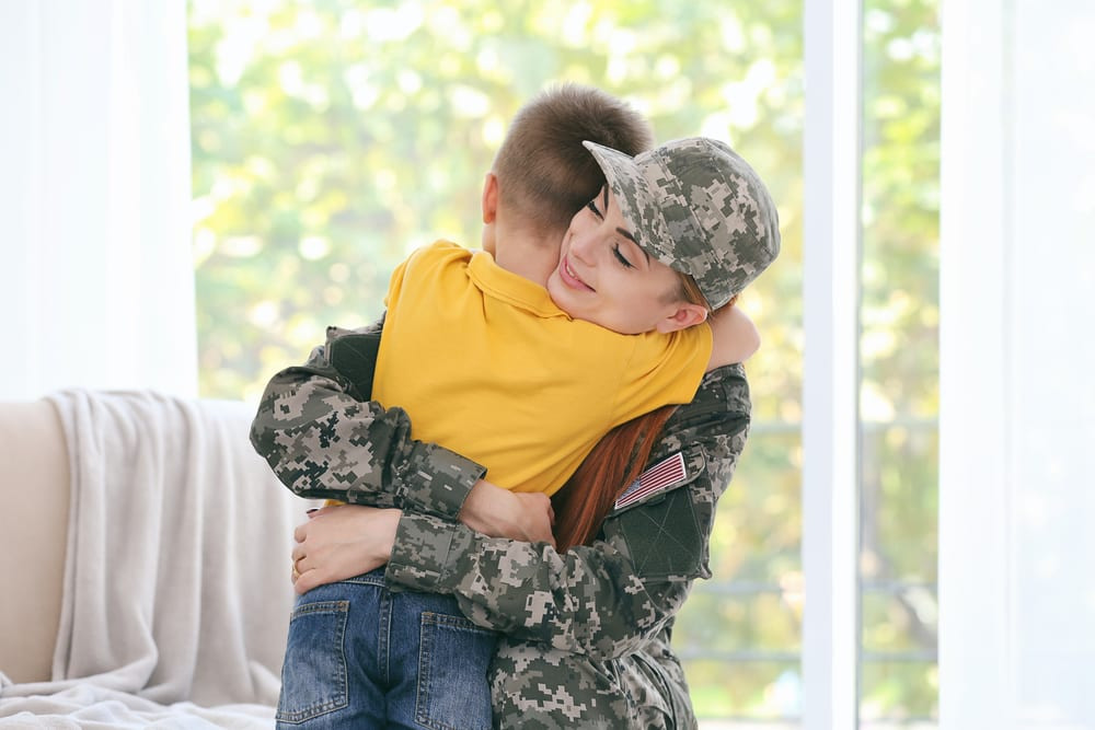 Soldier hugging her son in their home