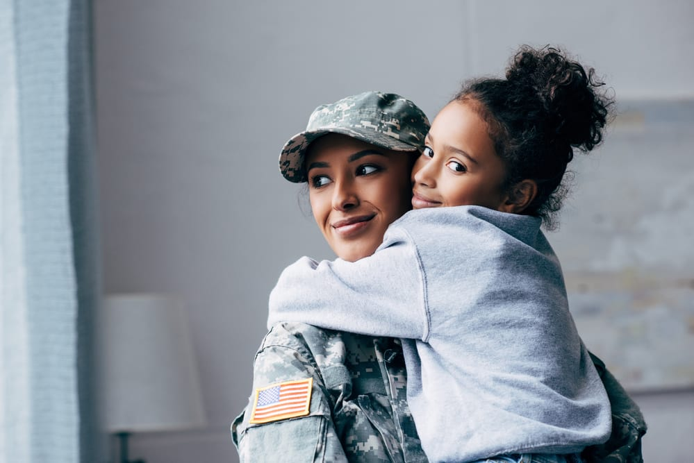 woman in the U.S. military hugging her daughter, both smiling