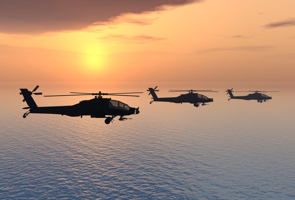 apache helicopters flying over the ocean at sunset