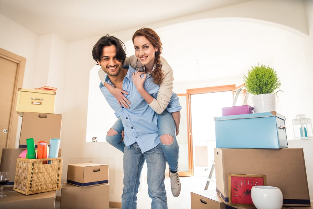 Smiling couple after moving into a new home, surrounded by boxes