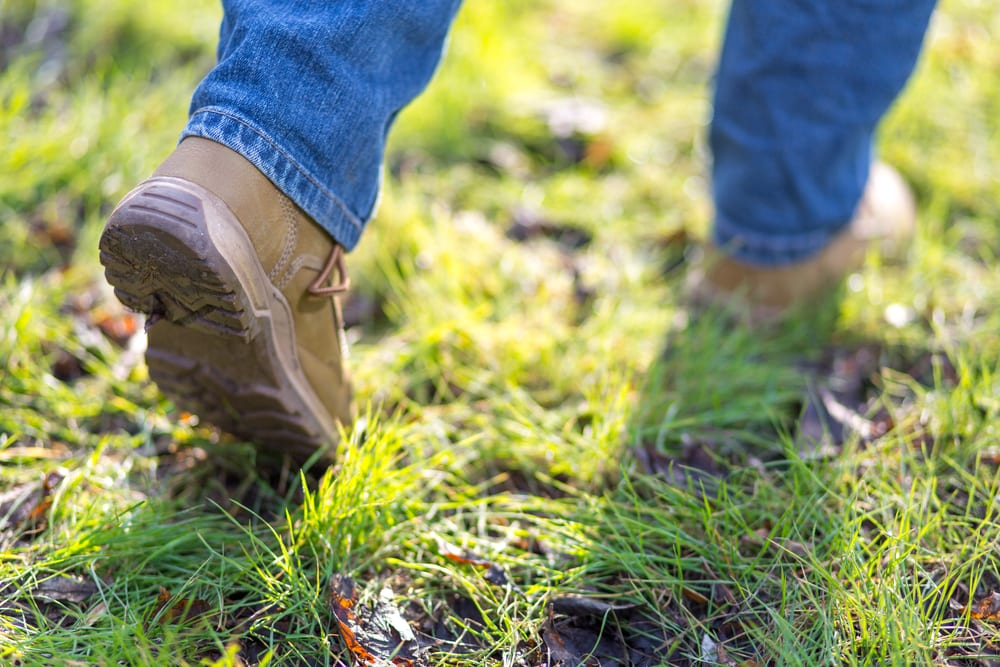 boots walking away in grass