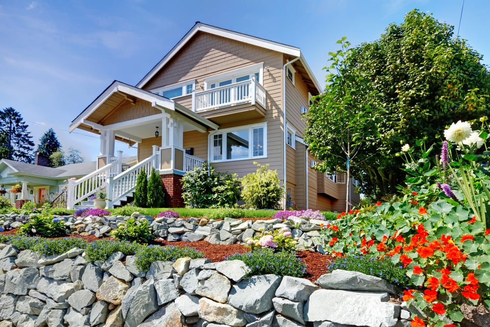 Two story beige nice house on the hill with rock walls and flowers.
