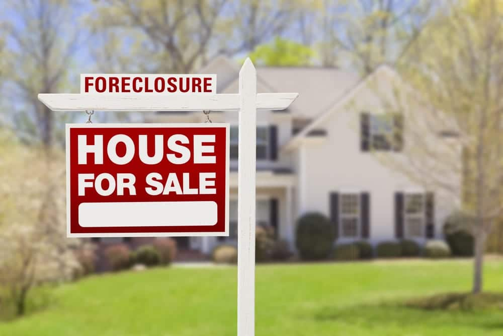 foreclosure for sale sign in front of beautiful house