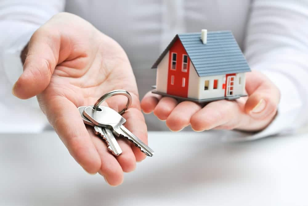 Hands holding out keys and a small model of a house