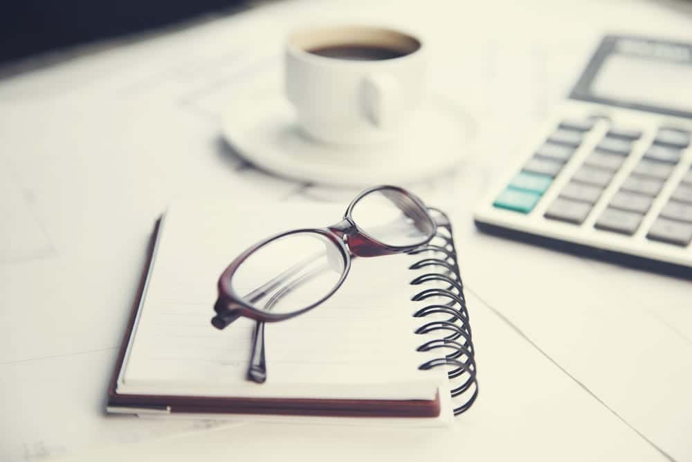 Notebook, glasses, coffee cup, and calculator