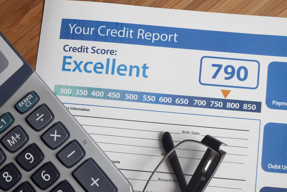 Close-up of calculator and credit report revealing 790 credit score