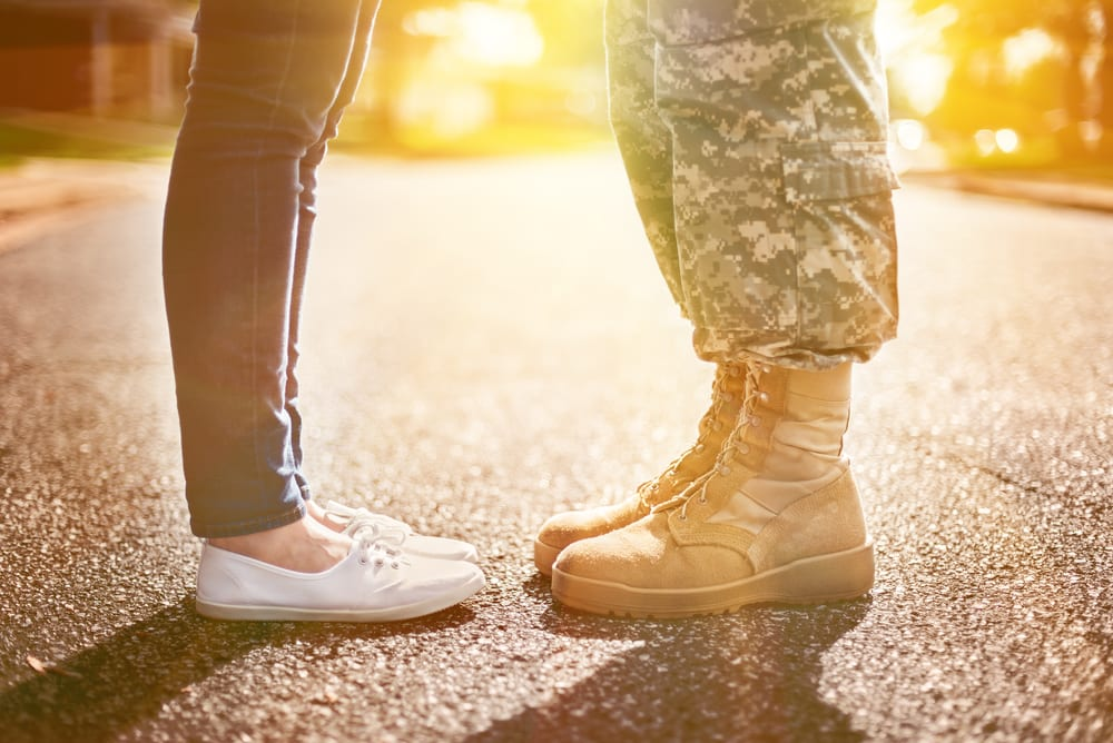 Close-Up of Two Pairs of Feet, One in Jeans and Keds, the Other in Army Combat Gear