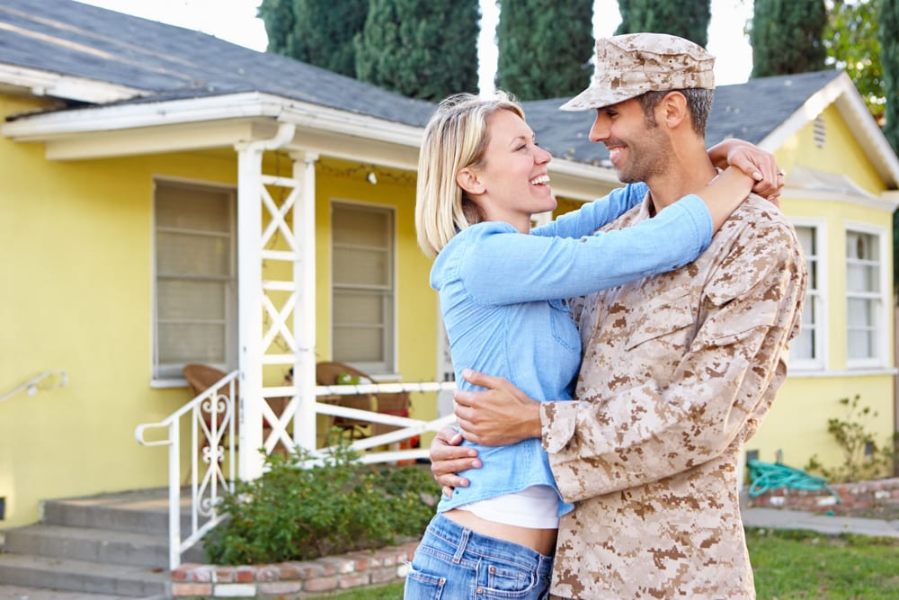 Military husband and wife smiling and embracing in front yard