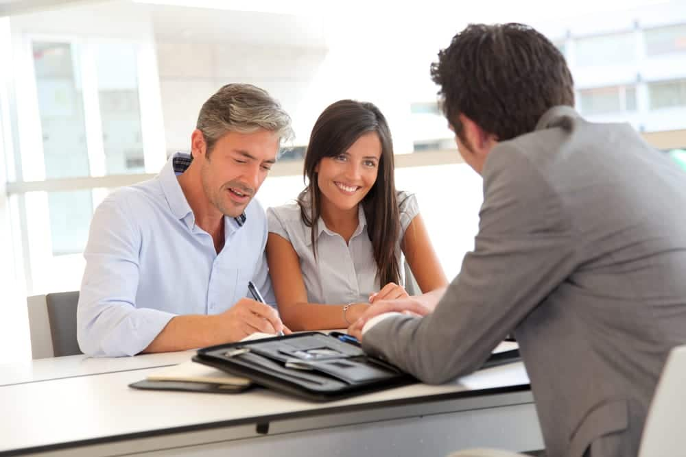 Couple signing papers in an office with the guidance of mortgage lender