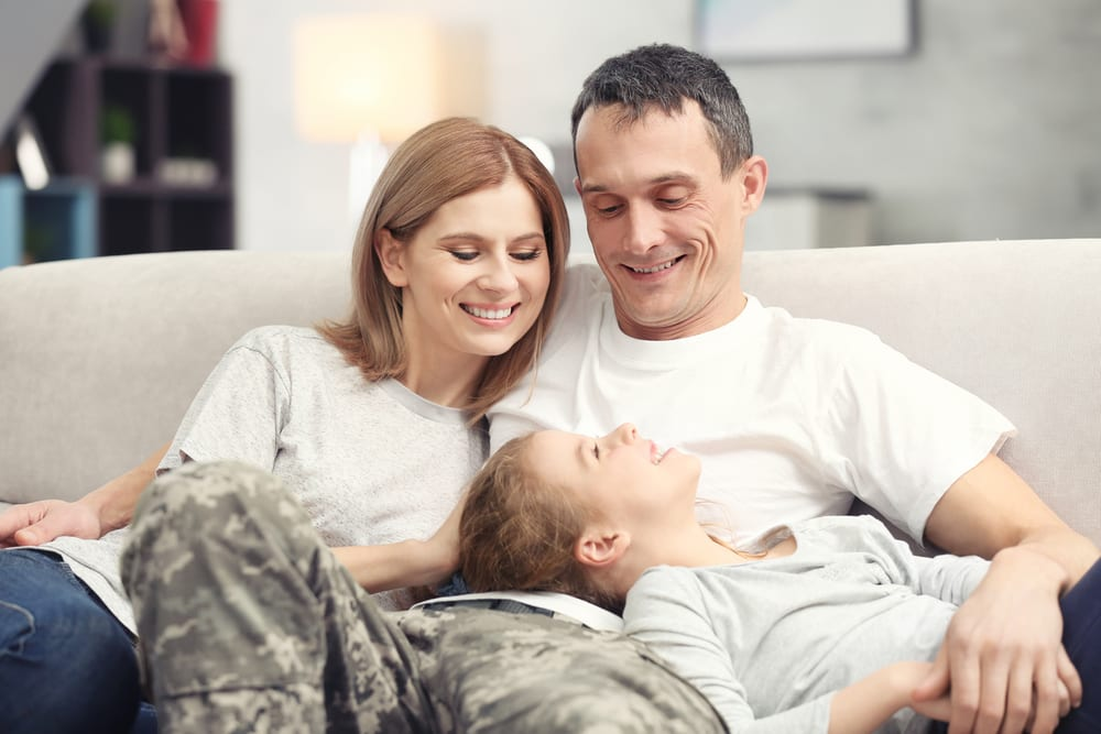 Father in camo pants relaxing on couch at home with wife and daughter