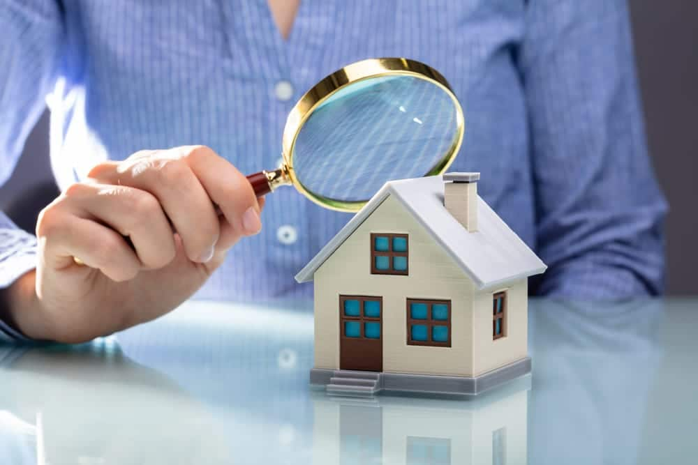 woman looking at home model with a magnifying glass