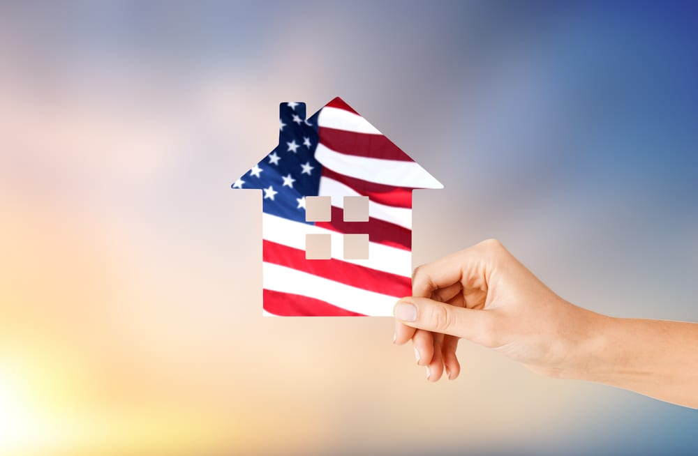 Hand holding up cut-out house shape with American flag pattern